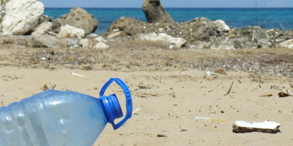 A plastic bottle lying on a beach.