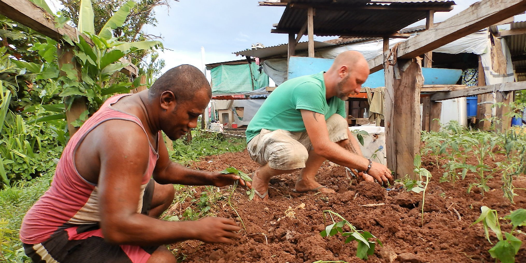 Two men working in a garden together.