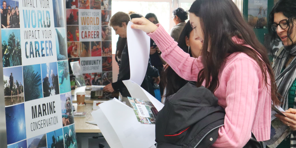 A prospective volunteer perusing program information at a GVI stand.