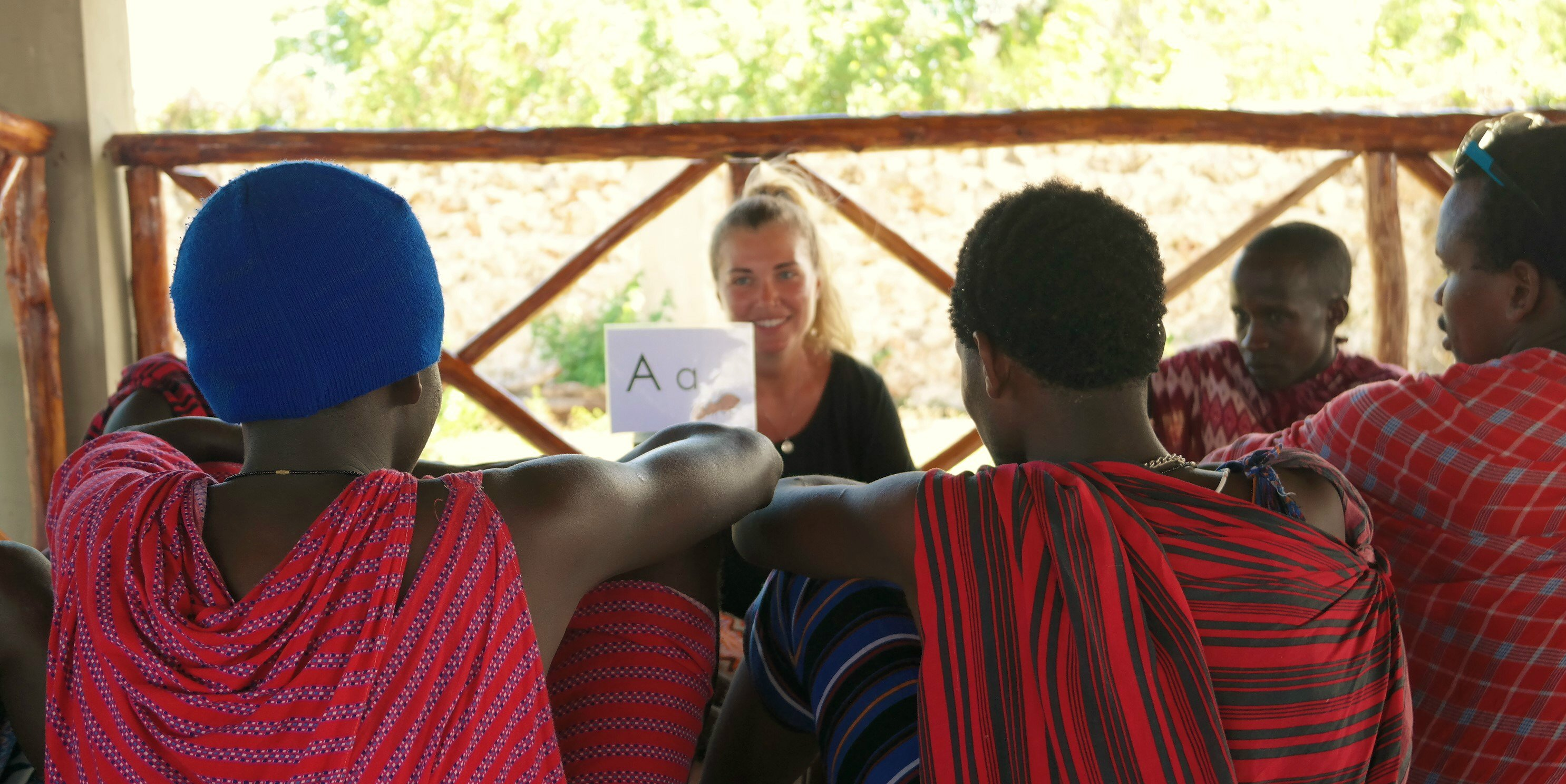 A volunteer teaching in Tanzania works with Masaai people on their English.