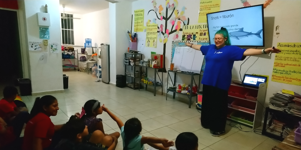 A volunteer teaching children about sharks.