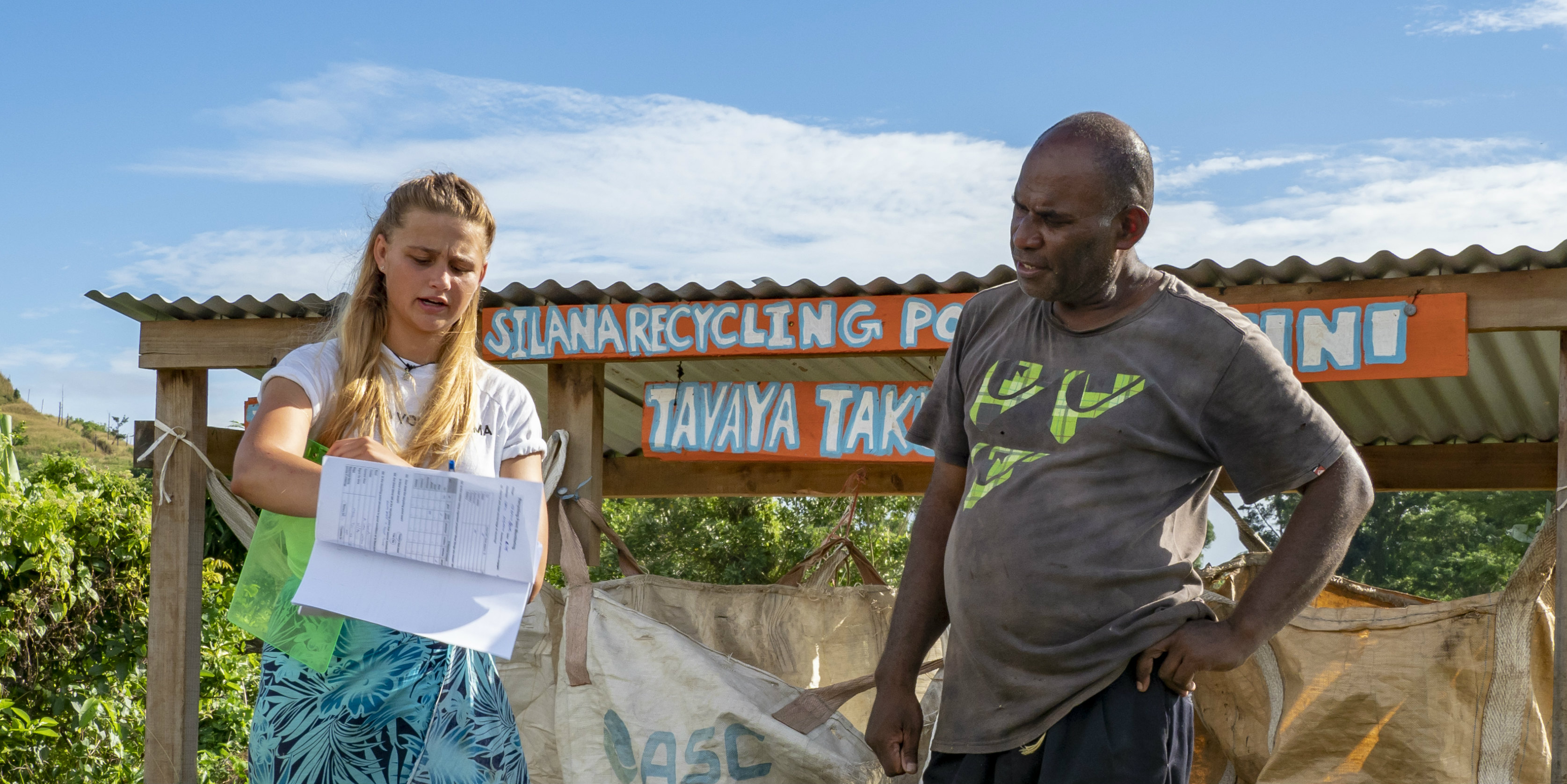 A GVI participant collaborates with a local community member on a recycling program. Being a global citizen involves genuine engagement with local communities.