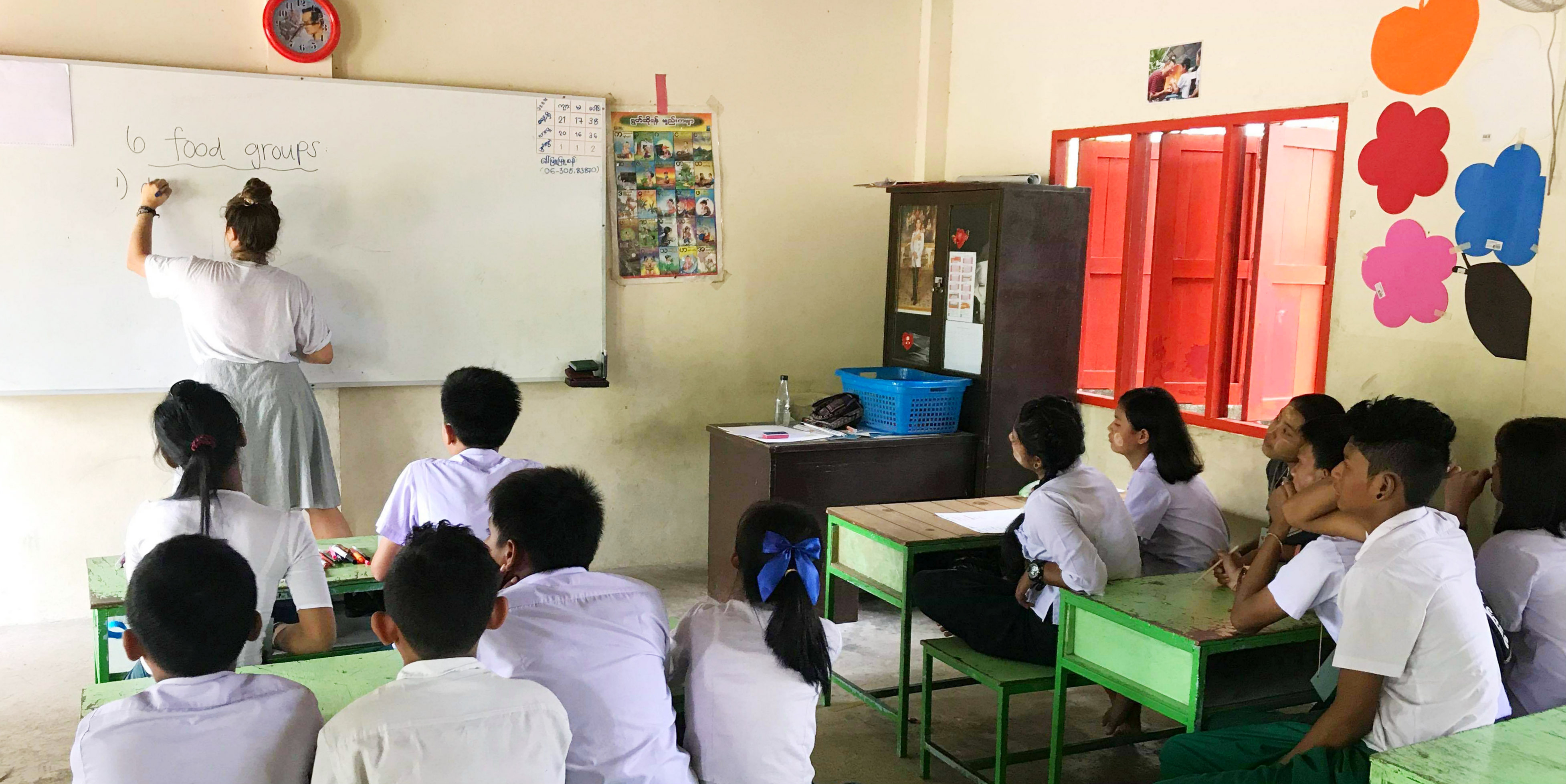 A teach English in Thailand participant explains the different food groups to a class of learners.