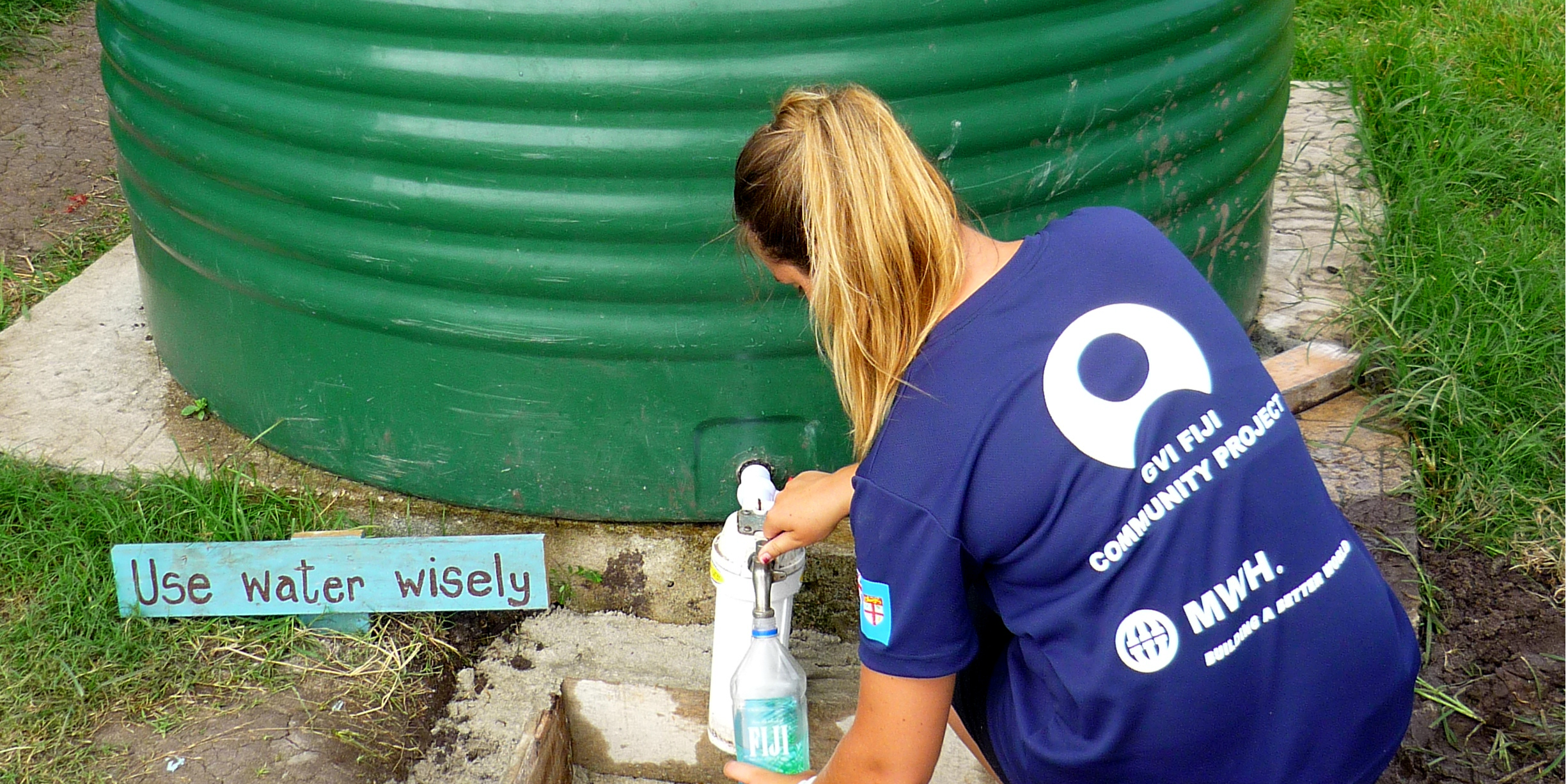 A participant collects water from a rainwater collection point in Dawasamu, Fiji as part of their community development internship.