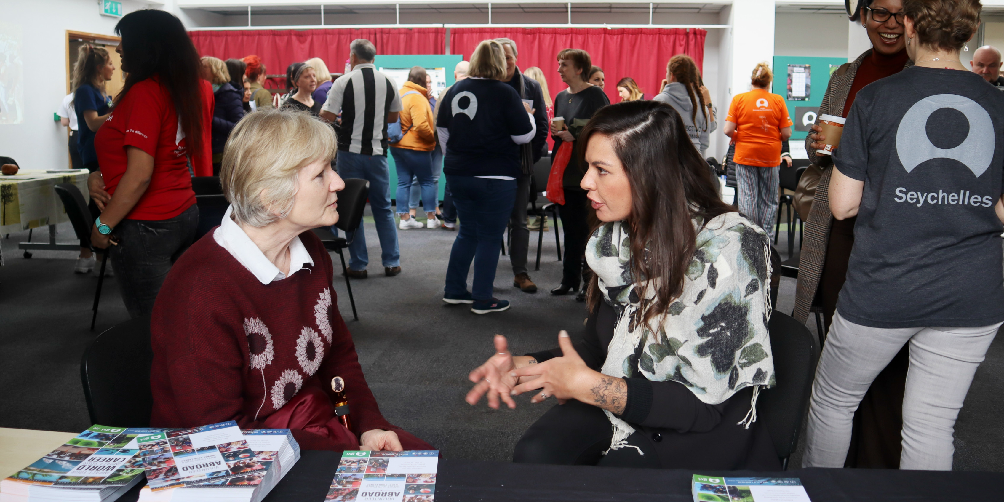 A GVI staff member chats to a parent about the many teen volunteering opportunities with GVI, at an Open Day in London.