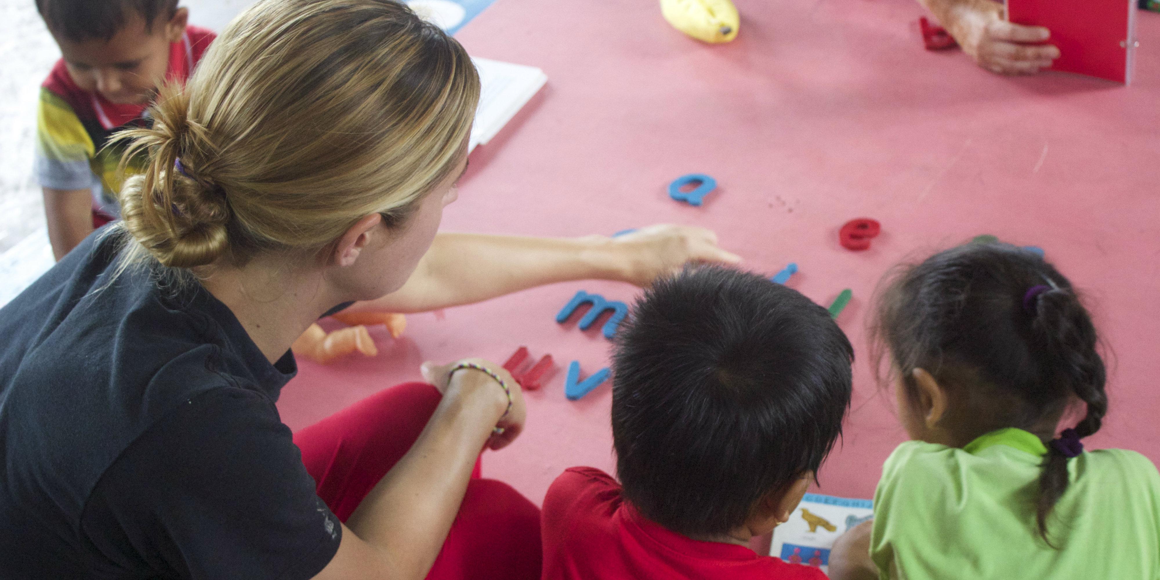 A TEFL teacher plays a word game with learners on a GVI program.