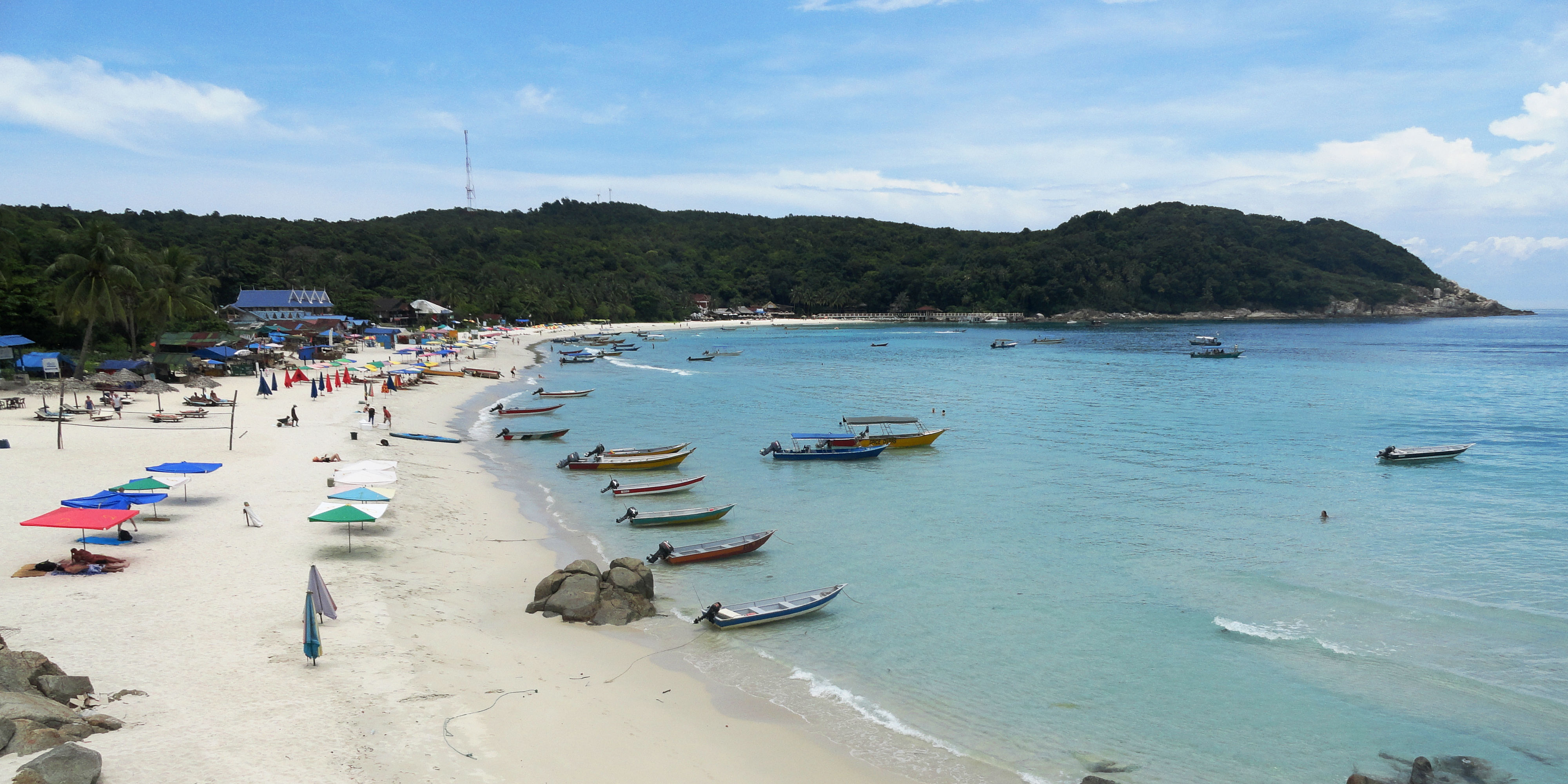 A shot of a beach on the Perhentian Islands shows colourful fishing boats and ebach umbrellas. By promoting sustainable tourism, scenes like this will remain untarnished.