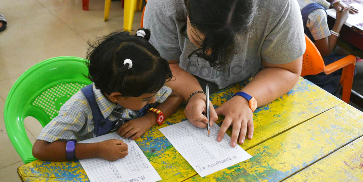 A teach English abroad volunteer works through a worksheet with a young learner.