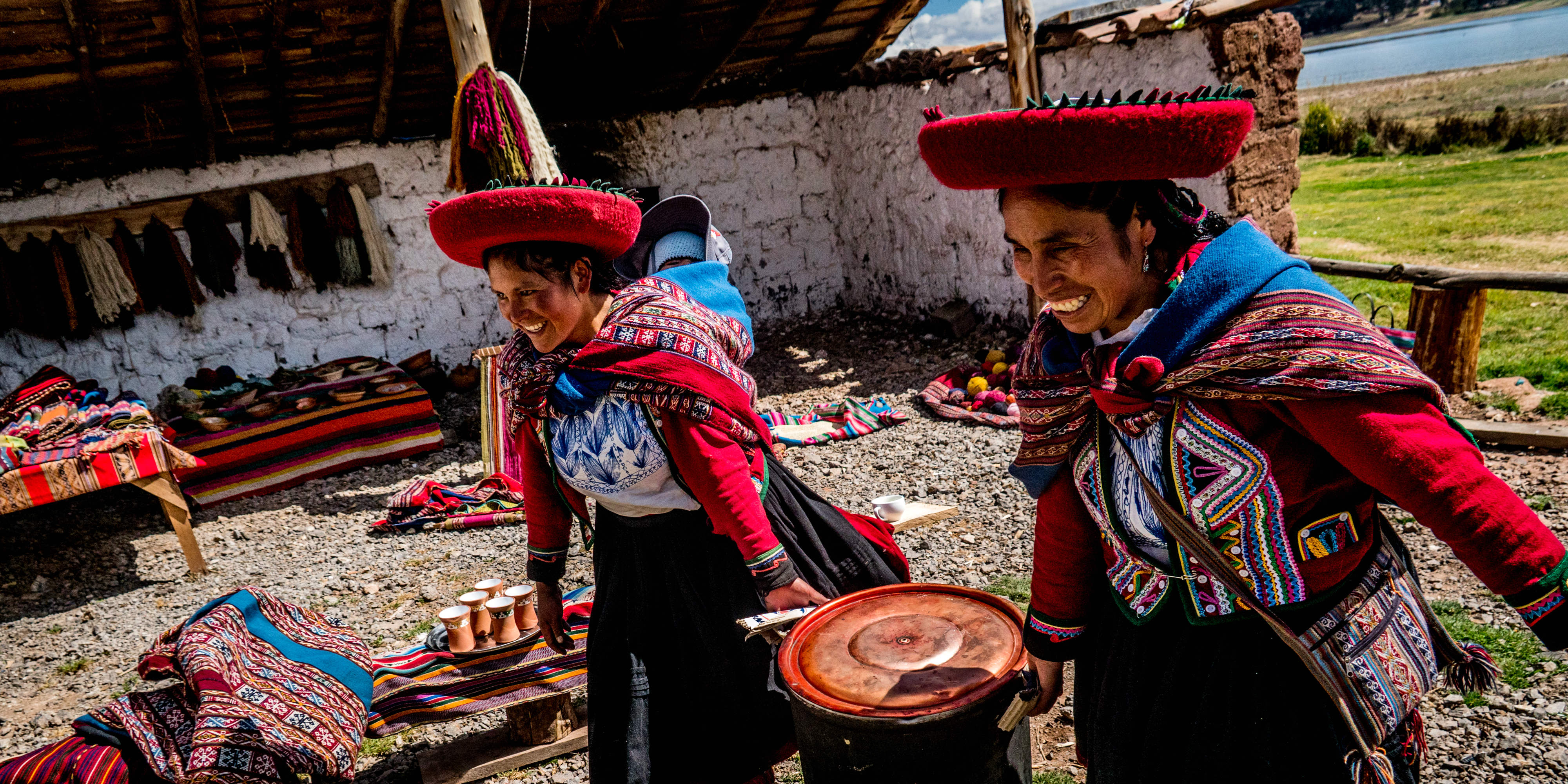 Two quechua people prepare a vat of dye for the traditional method of dyeing wool.