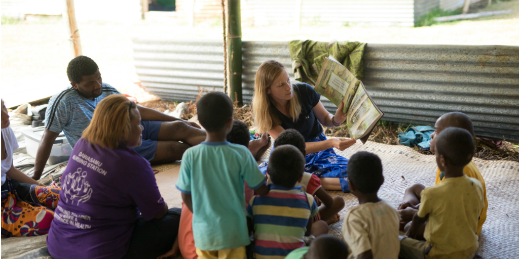 GVI volunteer reading a story to children in Fiji