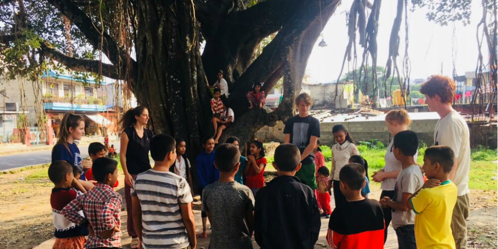 Childrn from Pokhara gather under a large tree with volunteers from GVI.