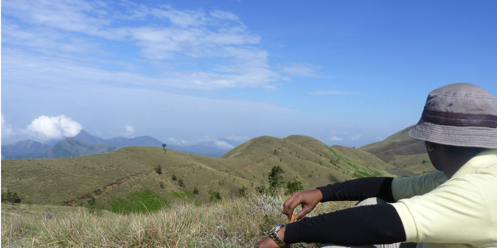 Volunteer sitting on a hill top looking at the view