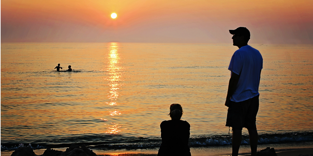 Children swimming at a beach with their parents looking on from the shore