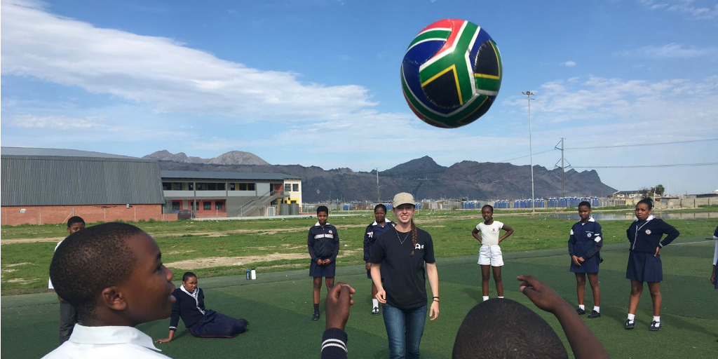 A volunteer playing soccer with students in Cape Town, South Africa.