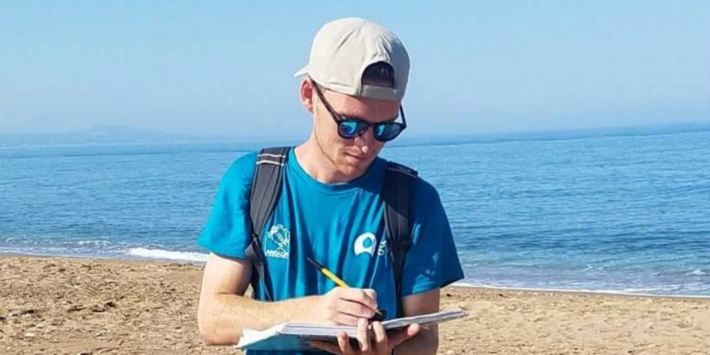 A volunteer writing on a clipboard with the ocean in the background.