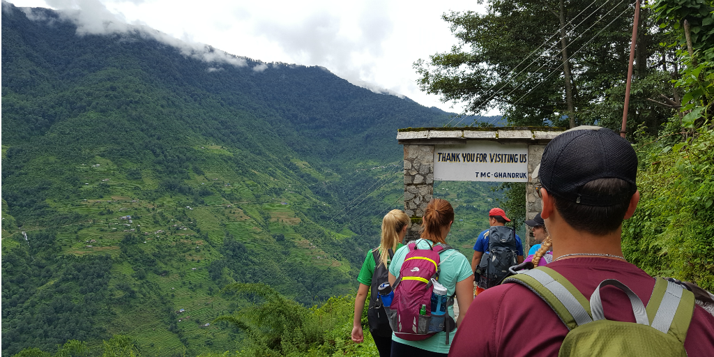 A row of hikers walking towards an arch on a mountain pathway in Nepal.