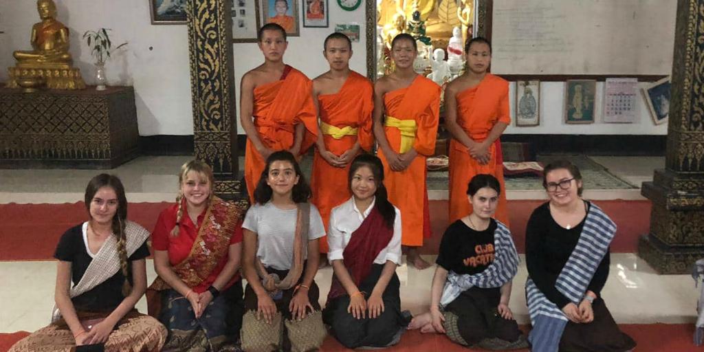 Volunteers kneeling in front of novice Buddhist monks in temple in Thailand.