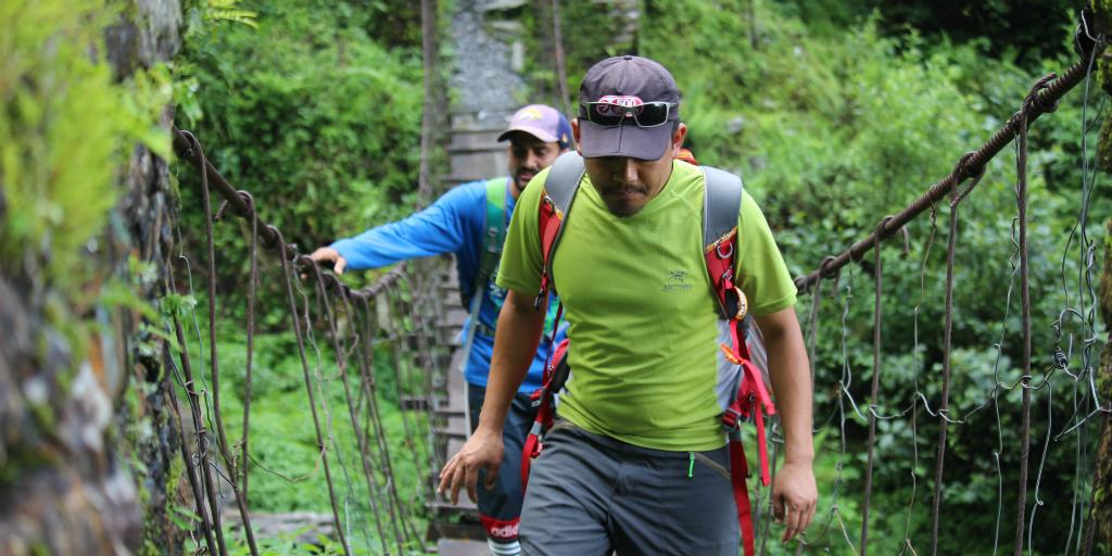 Two men walking across a suspension bridge in the jungle.