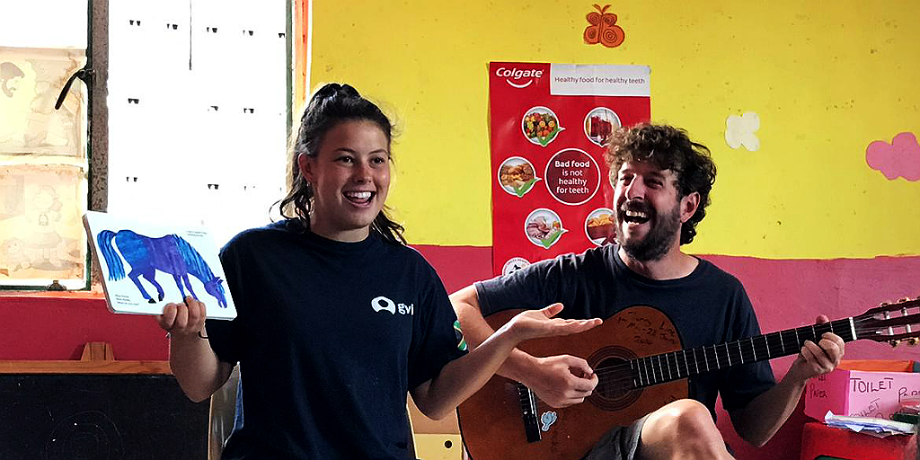 two volunteers lead a song and story time session while contributing to charity work abroad