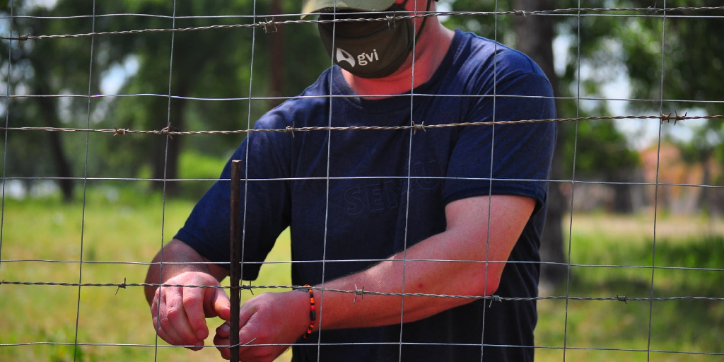 A GVI volunteer in limpopo doing fence repairs